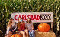 Gabriella Lazaro, Abigail Gant, and Allison Bell sit among the corn and pumpkins.