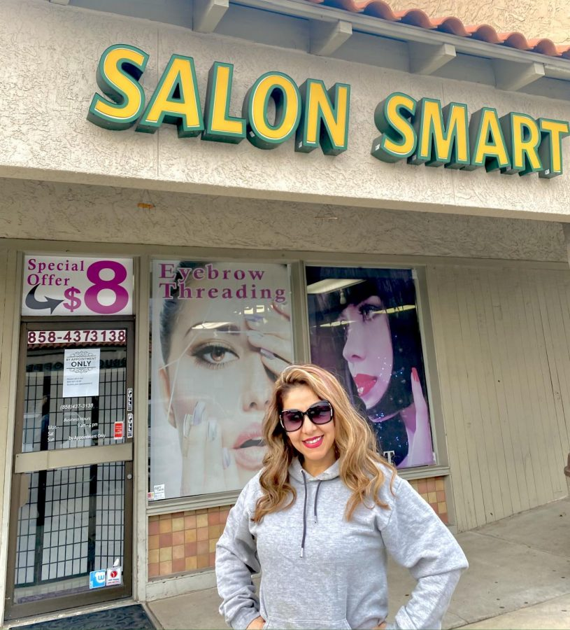 Benni Takloo, owner of Salon Smart, standing in front of her business, proud and confident.